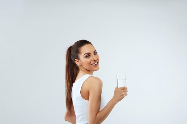 아름 다운 여자의 초상화는 물 잔을 보유하고있다. 물 마시기. 물 잔 소녀입니다. 다이어트 개념