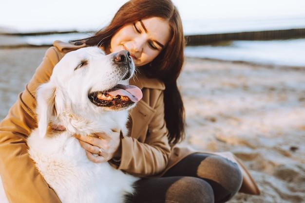 Портрет красивой женщины, обнимающейся со своей золотой ретривер собакой на море