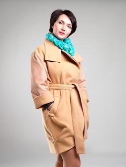 녹색 스카프와 베이지 색 가을 코트에서 아름 다운 여자의 초상화