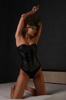 검은 가죽 코르셋과 베네치안 마스크를 쓴 아름다운 여성의 초상화