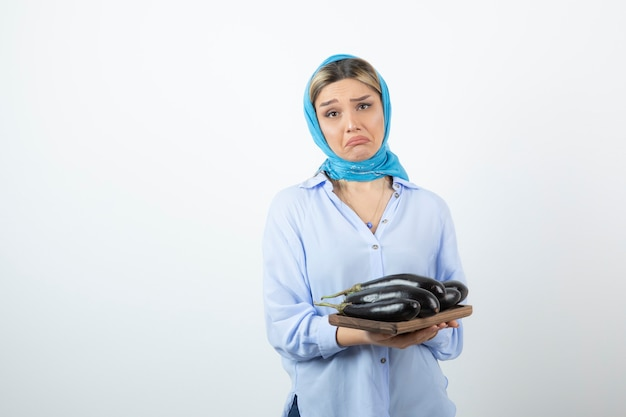 悲しい表情でナスを保持している青いショールの美しい女性の肖像画