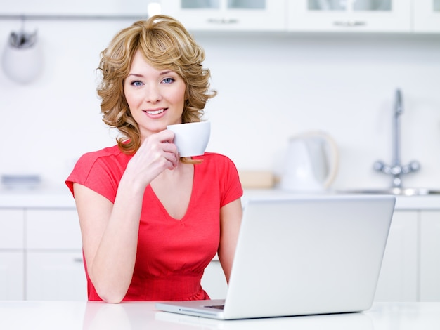 Портрет красивой женщины в повседневной одежде, сидящей на кухне с чашкой кофе и ноутбуком