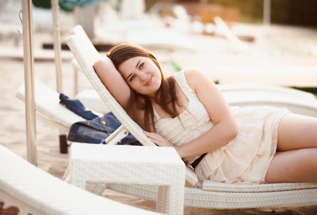 ビーチでサンベッドに横たわるドレスを着た美しい女性の肖像画