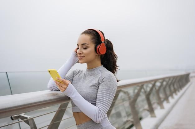ヘッドフォンで音楽を聴いてスタイリッシュなスポーツウェアの美しい女性の肖像画