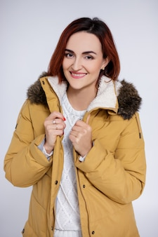 灰色の背景の上にポーズをとって暖かい冬のジャケットの美しい女性の肖像画