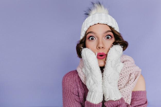Портрет красивой женщины в белых рукавицах, изолированных на фиолетовой стене. очаровательны брюнетка девушка в шляпе, выражая удивленные эмоции.