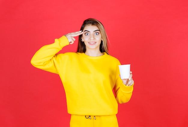 Портрет красивой женщины в желтом наряде, позирующей с чашкой чая