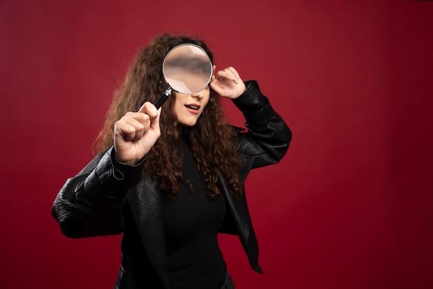 虫眼鏡を通して見ている美しい女性の肖像画。