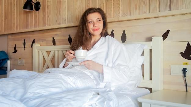 朝、ベッドに横になってコーヒーを飲む美しい女性の肖像画