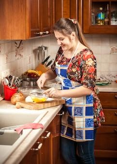 Портрет красивой женщины, смешивающей желток на кухне