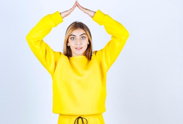 Портрет красивой женщины модели стоя и позирует в желтой футболке