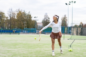 Portrait of beautiful woman playing tennis outdoor