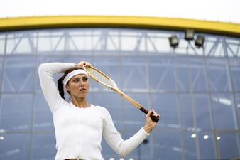 Портрет красивой женщины, играя в теннис на открытом воздухе