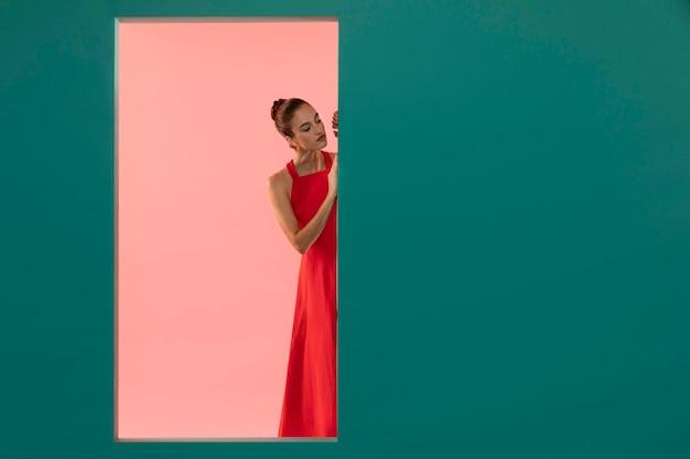 Портрет красивой женщины, позирующей в струящемся красном платье с копией пространства