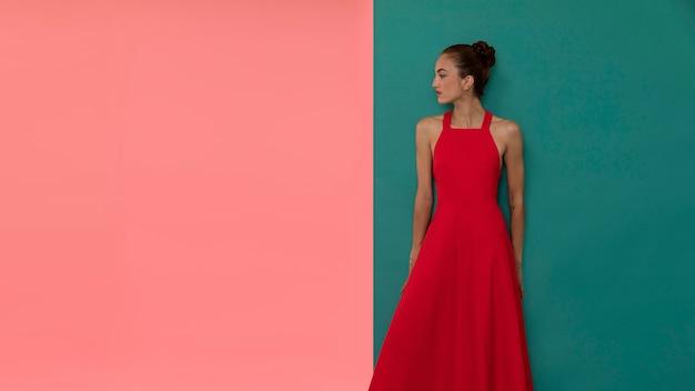 コピースペースと流れるような赤いドレスでポーズをとって美しい女性の肖像画