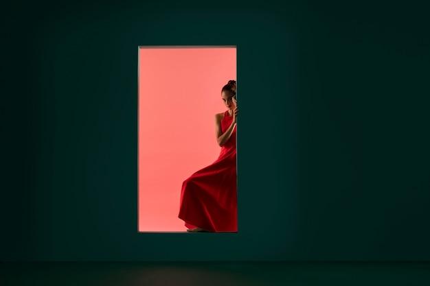 流れるような赤いドレスでポーズをとる美しい女性の肖像画