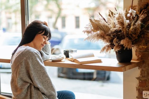 카페에서 휴식을 취하면서 책을 읽는 아름다운 여성의 초상화.