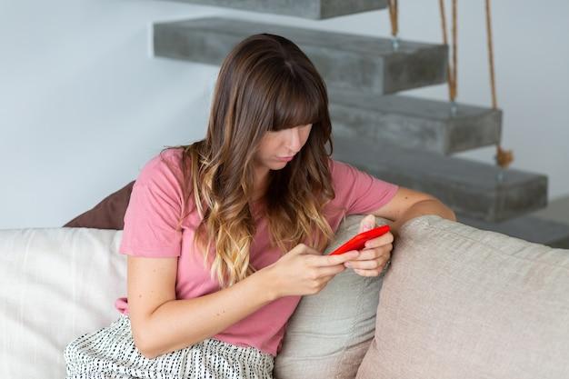 自宅のソファでリラックスした美しい女性の肖像画。スマートフォンを手に持った女性。