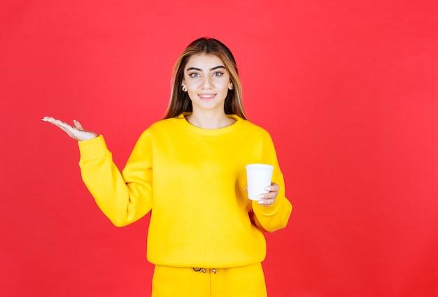 赤い壁にお茶のプラスチックカップを示す美しい女性の肖像画