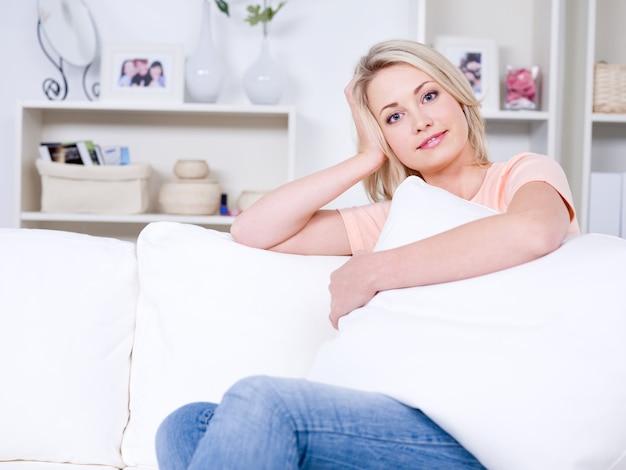 Портрет красивой женщины, сидящей на удобном диване у себя дома