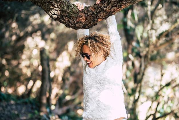 Портрет красивой женщины улыбается и любит играть с деревом