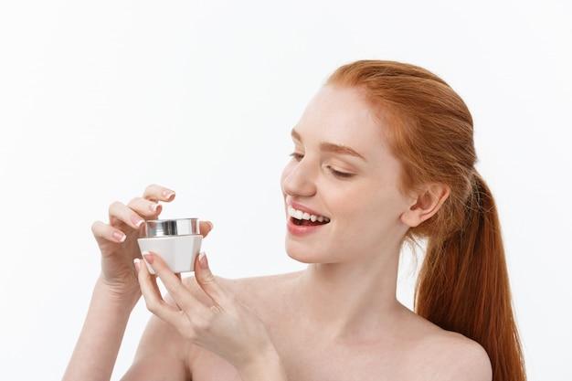 얼굴 크림을 복용하는 동안 웃는 아름다운 여자의 초상화는 흰색에 고립