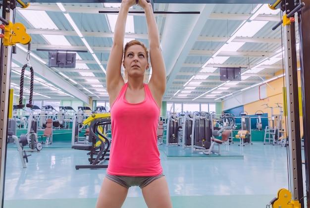 フィットネスセンターでクロスフィットトレーニングを開始する前にスポーツバーで腕を伸ばしている美しい女性の肖像画