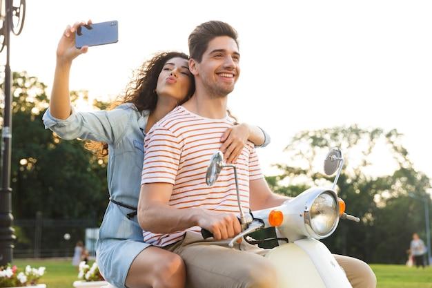 그녀의 남자 친구와 함께 도시 거리를 통해 오토바이를 타고있는 동안 스마트 폰에 셀카를 복용하는 아름 다운 여자의 초상화