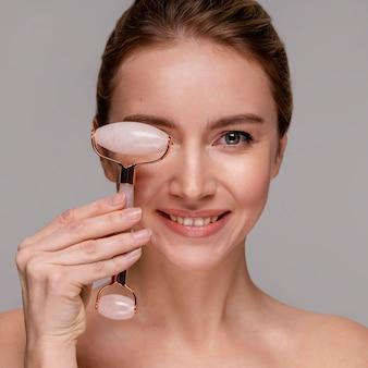 Портрет красивой женщины, использующей нефритовый ролик