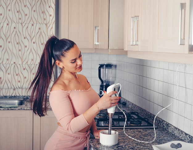 Портрет красивой женщины, используя ручной блендер и лососевых розовый топ и брюки на кухне.
