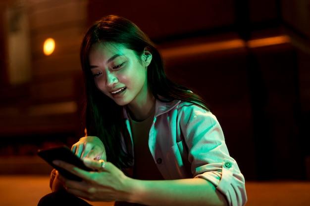 도시의 불빛에 밤에 스마트 폰을 사용하는 아름 다운 여자의 초상화