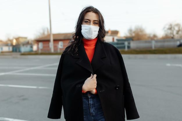 感染症からの保護として保護マスクを着用して通りを歩いている美しい女性の肖像画。屋外でインフルエンザの魅力的な不幸なモデル。