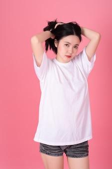 Портрет красивой женщины в белой футболке на розовом.