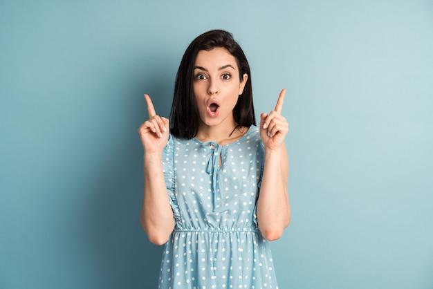 青い壁に分離されたコピースペースで親指を上に向けて幸せを表現する魅力的な水玉模様のドレスを着ている美しい女性の肖像画