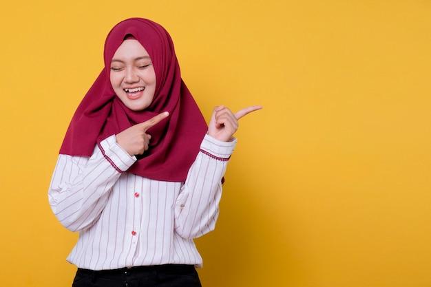 Портрет красивой женщины в хиджабе с закрытыми глазами, улыбкой и указательным выражением левой стороны