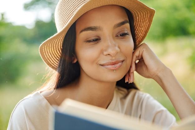 Портрет красивой женщины с пирсингом в губе и соломенной шляпе, читающей книгу, сидя на траве в зеленом парке