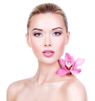 ピンクの花を持つ美しい女性の肖像画。健康な顔の肌を持つかなり大人の女の子。 -白い背景で隔離