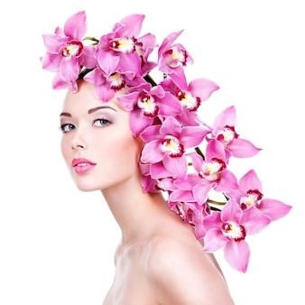 ピンクの花を持つ美しい女性の肖像画。健康な顔の肌を持つかなり大人の女の子。 -白い壁に隔離
