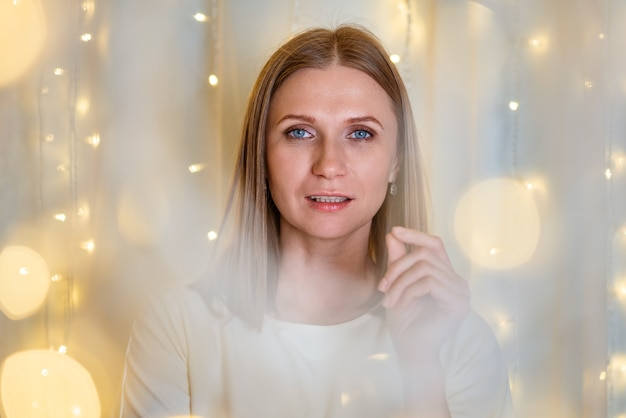 섬세한 톤 소녀의 파란 눈 근접 촬영 보케 화환을 가진 아름다운 여성의 초상화는 축하입니다...