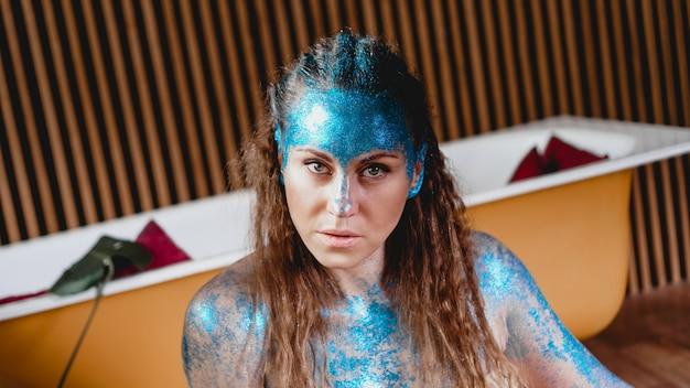 彼女の顔に青い輝きを持つ美しい女性の肖像画。フリークとエイリアンの概念。人は他の人とは異なります。個性