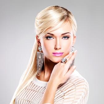 Портрет красивой женщины с ярким модным макияжем и длинными белыми волосами.