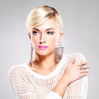 Портрет красивой женщины с ярким модным макияжем и белыми волосами.