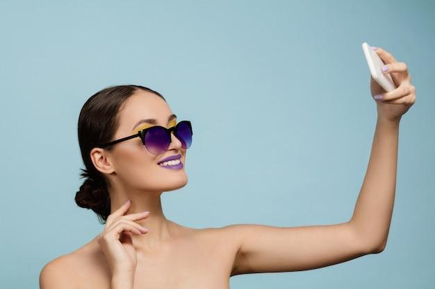 밝은 메이크업과 선글라스 블루 스튜디오 배경에 아름 다운 여자의 초상화. 세련되고 세련된 메이크업과 헤어 스타일. 여름의 색상. 미용, 패션 및 광고 개념. 셀카 만들기.