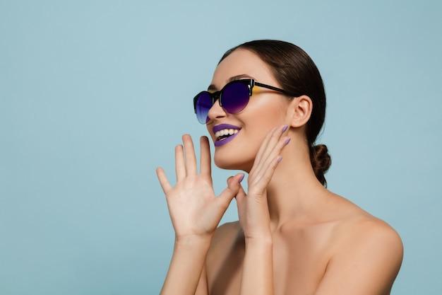 밝은 메이크업과 선글라스 블루 스튜디오 배경에 아름 다운 여자의 초상화. 세련되고 세련된 메이크업과 헤어 스타일. 여름의 색상. 미용, 패션 및 광고 개념. 누군가에게 전화를 겁니다.