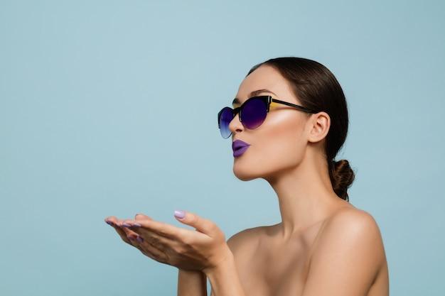 밝은 메이크업과 선글라스 블루 스튜디오 배경에 아름 다운 여자의 초상화. 세련되고 세련된 메이크업과 헤어 스타일. 여름의 색상. 미용, 패션 및 광고 개념. 키스 보내기.