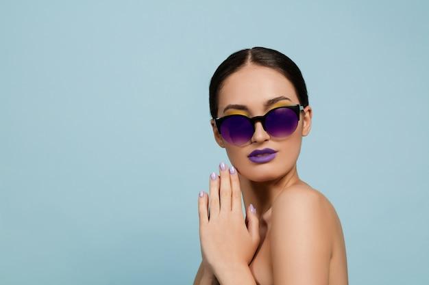 밝은 메이크업과 선글라스 블루 스튜디오 배경에 아름 다운 여자의 초상화. 세련되고 세련된 메이크업과 헤어 스타일. 여름의 색상. 미용, 패션 및 광고 개념. 진지하고 자신감이 있습니다.