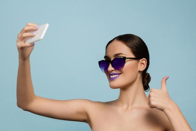 밝은 메이크업과 블루 스튜디오에 선글라스와 아름 다운 여자의 초상화