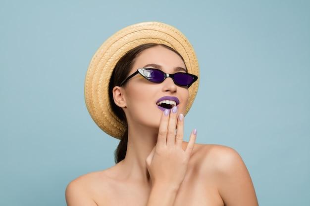 밝은 메이크업, 모자와 선글라스 블루 스튜디오 배경에 아름 다운 여자의 초상화. 세련되고 세련된 메이크업과 헤어 스타일. 여름의 색상. 미용, 패션 및 광고 개념. 놀랐습니다.