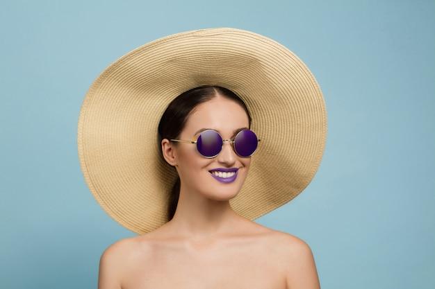 밝은 메이크업, 모자와 선글라스 블루 스튜디오 배경에 아름 다운 여자의 초상화. 세련되고 세련된 메이크업과 헤어 스타일. 여름의 색상. 미용, 패션 및 광고 개념. 웃음.