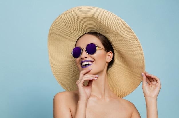 青いスタジオの背景に明るいメイク、帽子、サングラスの美しい女性の肖像画。スタイリッシュでファッショナブルなメイクとヘアスタイル。夏の色。美容、ファッション、広告のコンセプト。笑う。
